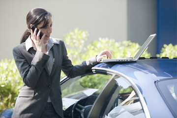 Businesswoman next to car with laptop talking on smartphone