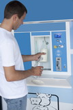 Man filling milk bottle at cooler