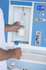 Closeup of man's hands filling milk bottle at cooler