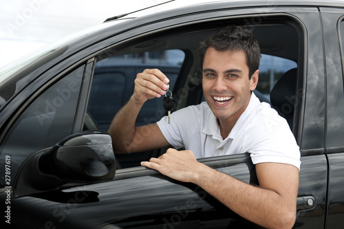 Happy hispanic man in his new car showing key