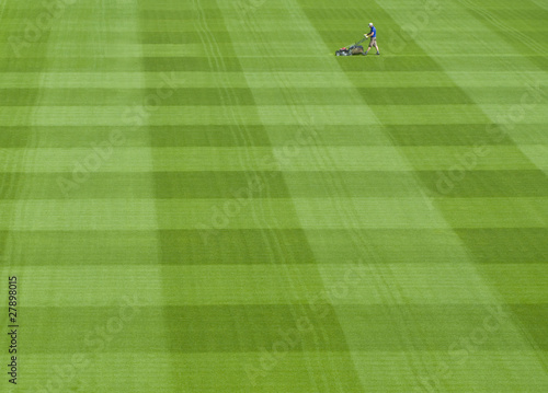 Groundskeeper mowing green grass of sports field