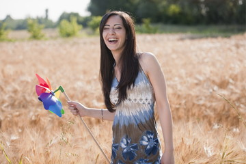 Young woman holding pinwheel in wheat field