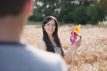 Young woman with man holding pinwheel in wheat field