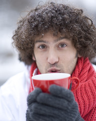 Portrait of young man blowing on cup of hot beverage on winter day