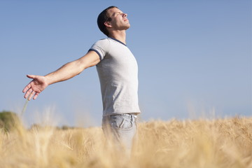 Man looking up with arms stretched out in wheat field
