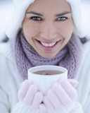 Portrait of young woman holding cup of hot tea on winter day