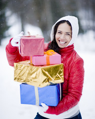 Portrait of young woman carrying presents on winter day