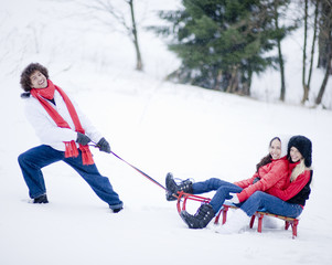 Young man pulling young women on sled in snow