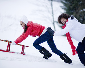 Happy young couple in snow pushing sled