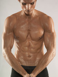Muscular young man with wet chest, studio shot
