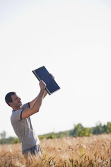 Man holding up solar panel in wheat field