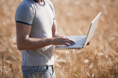 Man's torso with laptop computer in wheat field