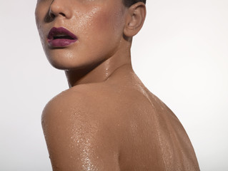 Cropped view of young wet woman wearing purple lipstick, studio shot