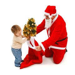 Little boy puts small tree in Santa's bag
