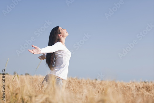Woman with arms stretched out in wheat field