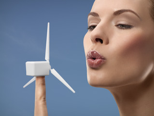 Young woman blowing wing turbine on finger, studio shot