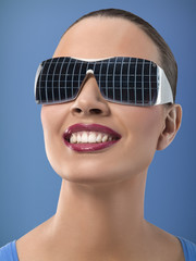 Young woman wearing sunglasses with reflection of solar panels, studio shot