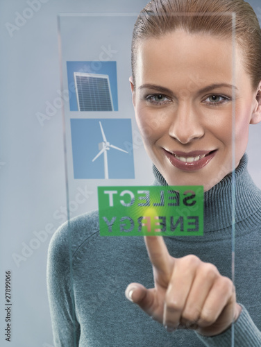 Young woman selecting alternative energy, studio shot