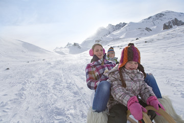 Mother and children sledding down mountain on winter day