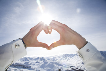 Close-up of woman's hands making heart shape over snow-capped mountains