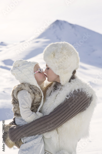 Mother and daughter kissing in mountains on winter day