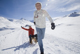 Senior couple sledding in mountains on winter day
