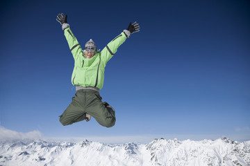 Mid adult man in ski gear jumping in midair