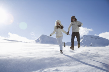 Young couple running in mountains on winter day
