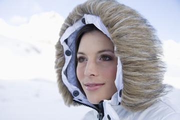Close-up of young woman wearing winter coat with fur hood