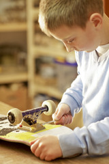 Young boy fixing skateboard