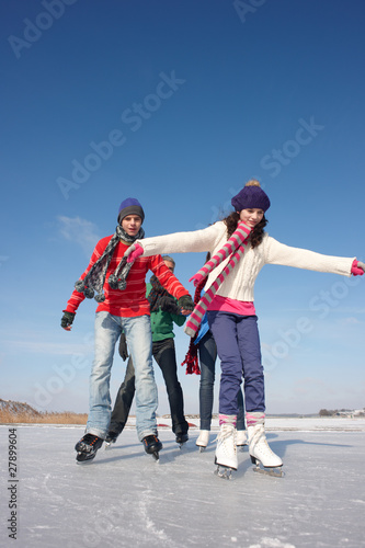 Family ice-skating on frozen lake together
