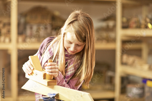 Young girl building a wooden craft