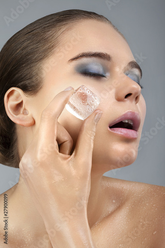 A woman cooling her face with an ice cube