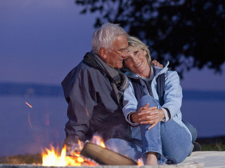 A senior couple sitting beside a campfire embracing