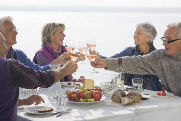 Five senior friends having lunch, raising their glasses