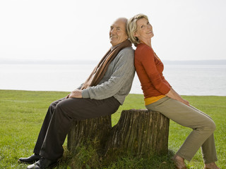 A senior couple sitting back to back on a tree stump
