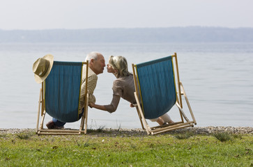 A senior couple sitting in deckchairs beside a lake, kissing