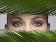 A woman's eyes looking out through green leaves