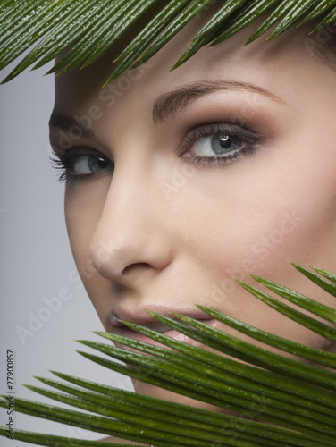 A woman's face behind green leaves