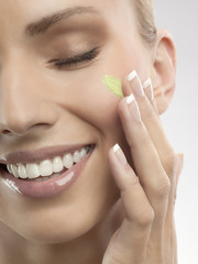 A woman putting green cream on her face