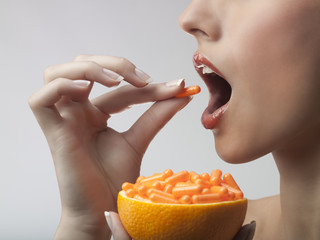 A woman taking vitamin c tablets