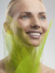 A woman holding green leaves made from net