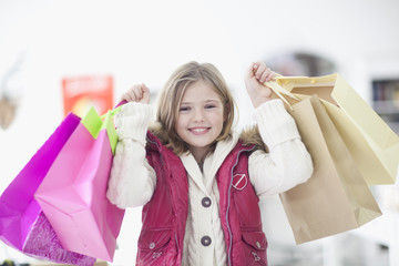 A young girl holding shopping bags