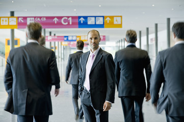 Businessmen at a conference centre, one looking to camera