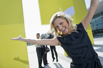 A blonde businesswoman with arms outstretched smiling, three colleagues in the background