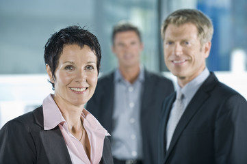A businesswoman with two male colleagues in the background
