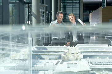 Two businessmen discussing an architectural scale model