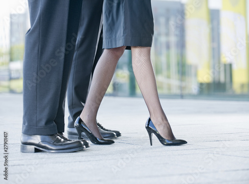Three businesspeople standing in a row, a businesswoman stepping forward