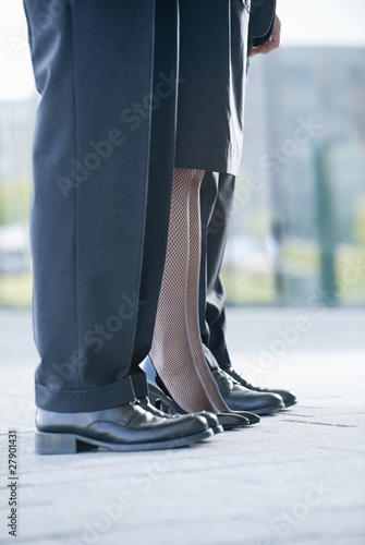 Two businessmen and a businesswoman standing in a row, close-up of their legs
