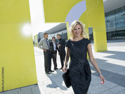 A blonde businesswoman outside a modern office building, three businessmen talking in the background